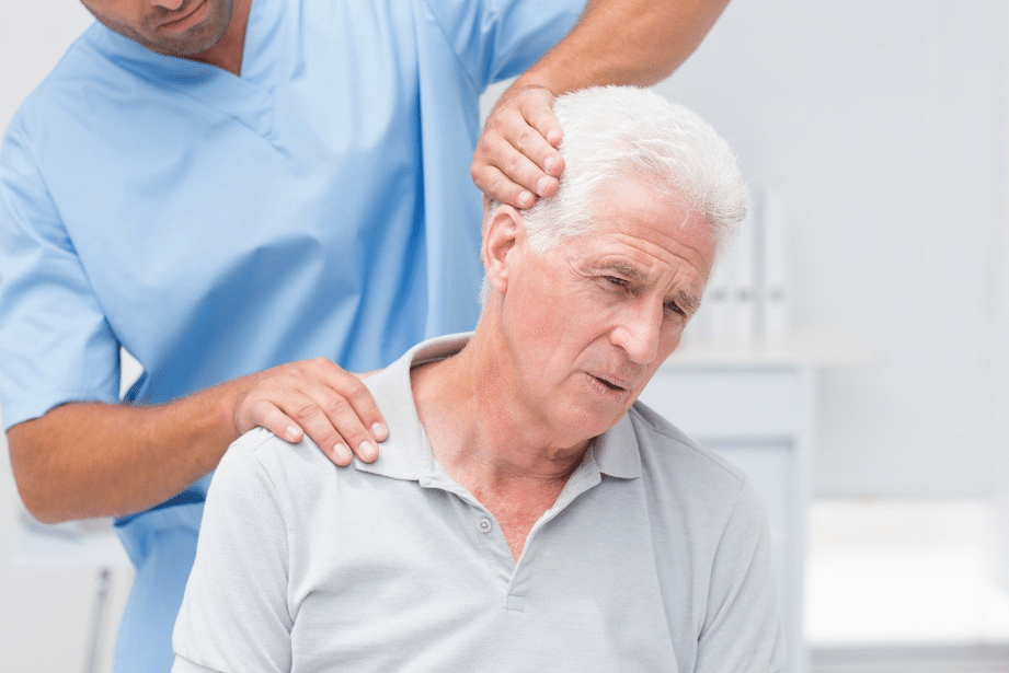 Physiotherapist giving physical therapy to senior male patient in clinic.