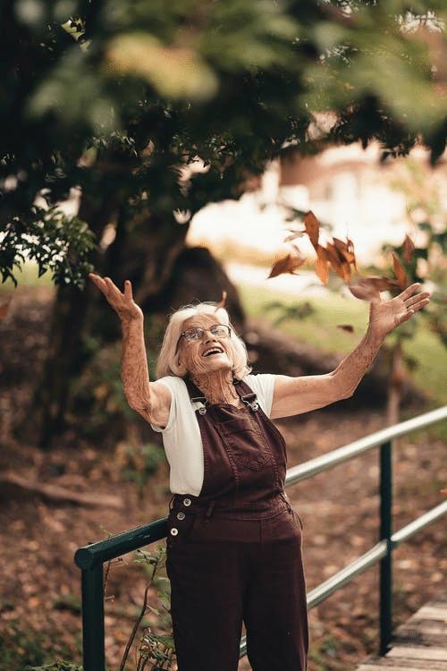 An elderly woman posing outdoors